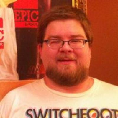 A rotund, bearded man with short, brown hair wearing a colorful T-shirt.