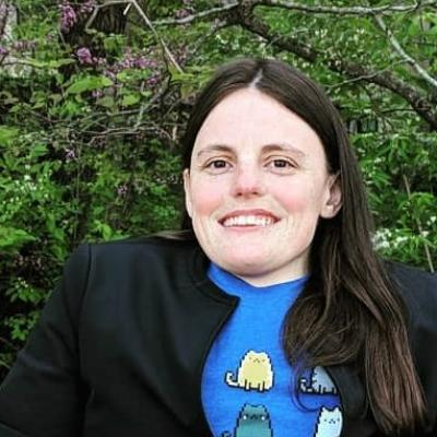 headshot of woman with long brown hair, blue a11y cats shirt and black blazer